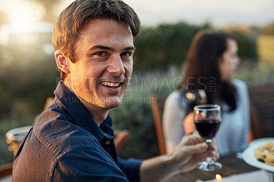Buy stock photo Portrait of a young man enjoying a meal with his friends outdoors