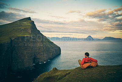 Buy stock photo Rearview shot of a carefree unrecognizable man seated on a hill looking out to a view of a lake and mountains