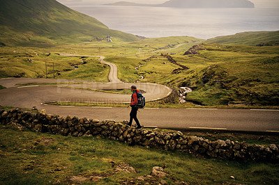 Buy stock photo Shot of a carefree young man walking on a empty road by himself outside in nature during the day