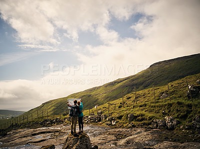 Buy stock photo Shot of two young carefree friends standing on a rock while reading a map to their next destination outside in nature
