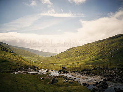Buy stock photo Shot of a breathtaking view of a little stream running through a mountain range outside in nature