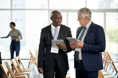 Buy stock photo Shot of two businessmen talking and using digital tablets together at a convention center