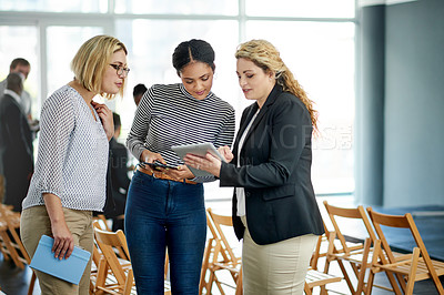 Buy stock photo Shot of a group of businesswomen using a digital tablet together at a convention center