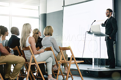 Buy stock photo Shot of a young businessman delivering a presentation at a conference