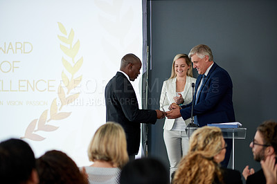 Buy stock photo Shot of a young businessman being awarded a prize during an awards giving ceremony at a conference