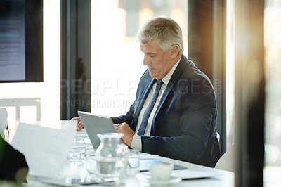 Buy stock photo Shot of a mature businessman using a laptop while sitting in on a boardroom meeting
