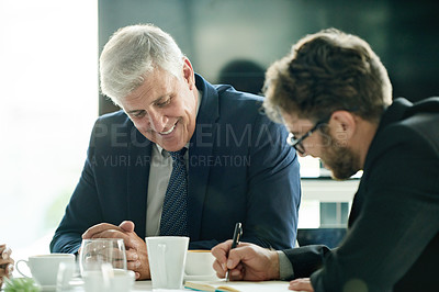 Buy stock photo Shot of two businessmen having a meeting in the boardroom