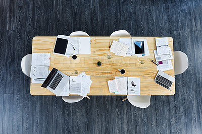 Buy stock photo High angle shot of paperwork and digital devices on a table in an office