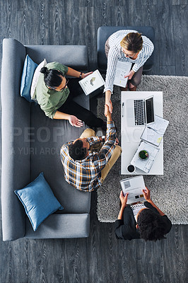 Buy stock photo High angle shot of businesspeople shaking hands during a meeting in an office