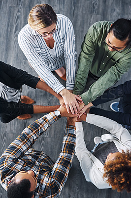 Buy stock photo High angle shot of a group of businesspeople joining their hands together in a huddle