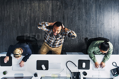 Buy stock photo High angle shot of a call centre agent taking a break while working alongside his colleagues in an office