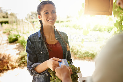 Buy stock photo Cropped shot of an attractive young woman making payment to a male customer at her stall at the farmers' market
