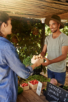 Buy stock photo Cropped shot of a handsome young man helping a female customer at his stall at the farmers' market