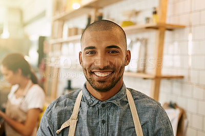 Buy stock photo Portrait of a cheerful young business owner standing inside of his coffees shop during the day