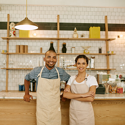 Buy stock photo Portrait of two young business owners and partners standing with their arms folded inside of their coffee shop during the day