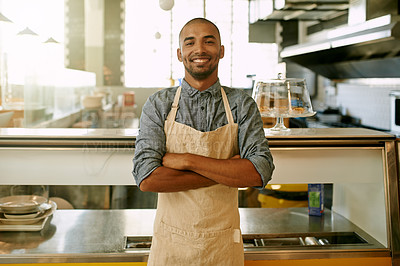 Buy stock photo Portrait of a confident young business owner of a cafe standing inside of his coffee shop with his arms folded during the day