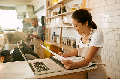 Buy stock photo Shot of a focussed young woman working on her laptop while making notes inside of a coffee shop during  the day