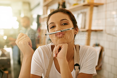 Buy stock photo Portrait of a carefree young woman holding a pencil in front of her while making a face inside of a coffee shop during the day