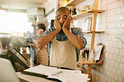 Buy stock photo Shot of a stressed out young man trying to get some paperwork done inside a coffee shop during the day