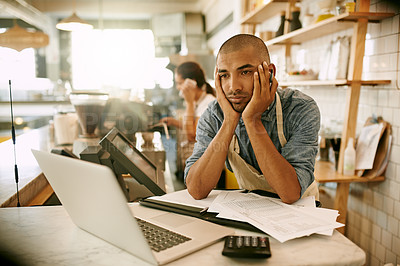 Buy stock photo Shot of a stressed out young man trying to get some paperwork done while holding his face and contemplating inside of a coffee shop