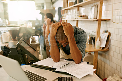Buy stock photo Shot of a stressed out young man trying to get some paperwork done while holding his head and contemplating inside of a coffee shop