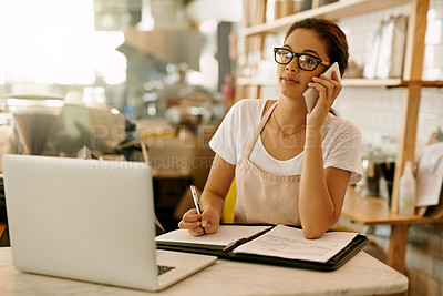 Buy stock photo Shot of a confident young woman making notes in a book while talking on her cellphone at work during the day