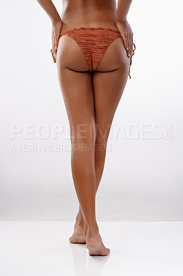 Buy stock photo Studio shot of an unrecognizable young woman in a bikini standing with her hands on her hips against a gray background