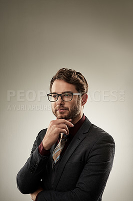 Buy stock photo Studio shot of a young handsome businessman posing against a grey background