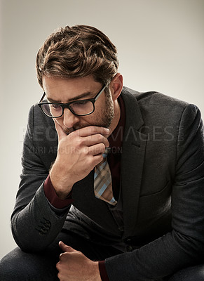 Buy stock photo Studio shot of a handsome young businessman looking worried while sitting against a grey background