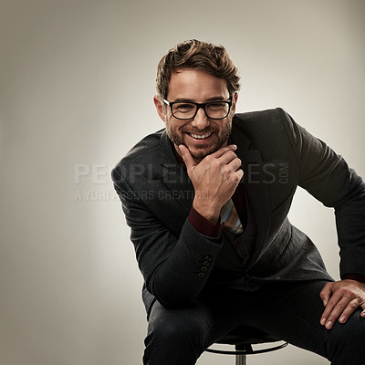 Buy stock photo Studio portrait of a handsome young businessman looking thoughtful while sitting against a grey background