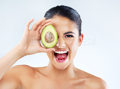 Buy stock photo Studio portrait of an attractive young woman covering her eye with an avocado against a gray background