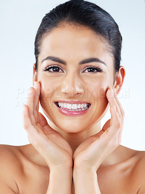 Buy stock photo Studio portrait of an attractive young woman feeling her skin against a gray background