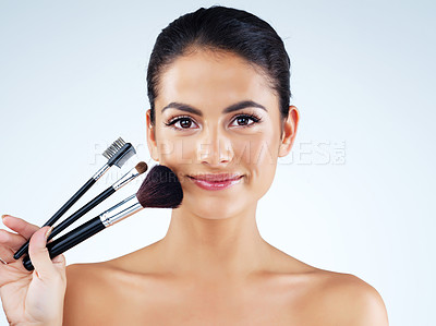 Buy stock photo Studio portrait of an attractive young woman holding makeup brushes against a gray background
