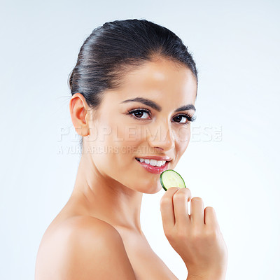 Buy stock photo Studio portrait of an attractive young woman eating a slice of cucumber against a gray background