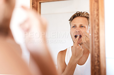 Buy stock photo Shot of a young man flossing his teeth at home