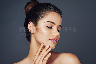 Buy stock photo Studio shot of a beautiful young woman with flawless skin posing against a blue background