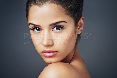 Buy stock photo Studio shot of a beautiful young woman with flawless skin posing against blue background