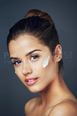 Buy stock photo Studio shot of a beautiful young woman with moisturizer on her face while posing against a blue background