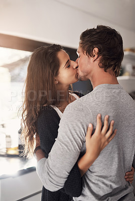 Buy stock photo Shot of an affectionate young couple kissing in the kitchen at home