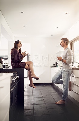 Buy stock photo Shot of a happy young couple enjoying a relaxing cup of coffee together in the kitchen