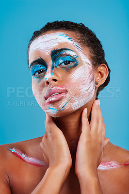 Buy stock photo Studio portrait of a beautiful young woman covered in face paint posing against a blue background