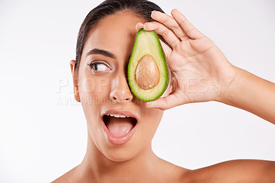 Buy stock photo Studio shot of a beautiful young woman holding half an avocado against a gray background