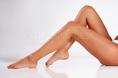 Buy stock photo Studio shot of an unrecognizable young woman's legs against a gray background