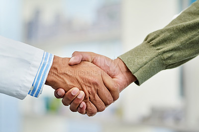 Buy stock photo Closeup shot of a doctor shaking hands with a patient in a hospital