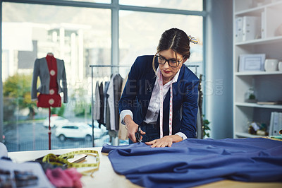 Buy stock photo Cropped shot of an attractive young fashion designer cutting fabric in her design workshop