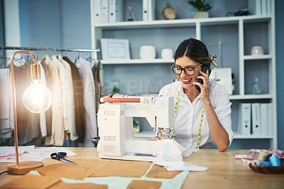 Buy stock photo Cropped shot of an attractive young fashion designer making a phonecall while working in her design studio