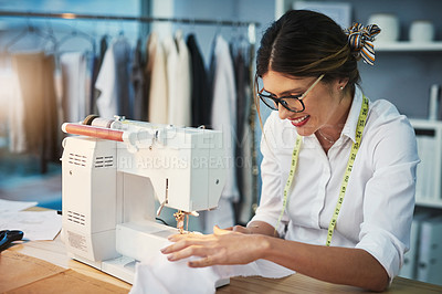 Buy stock photo Cropped shot of an attractive young fashion designer using a sewing machine in her design workshop