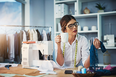 Buy stock photo Cropped shot of an attractive young fashion designer enjoying a coffee while working in her design studio