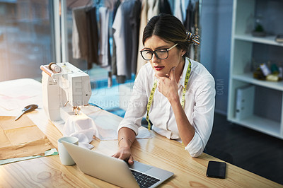 Buy stock photo High angle shot of an attractive young fashion designer working on her laptop in the design studio