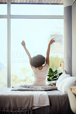 Buy stock photo Shot of a young woman sitting on the bed in the morning and stretching